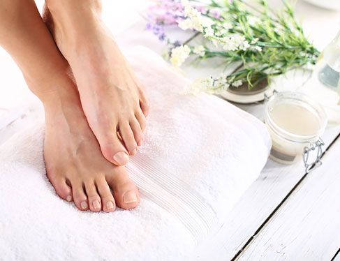 Close up of woman's feet on folded towel