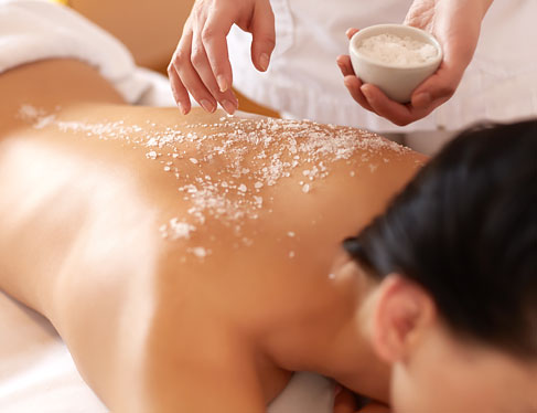 Sugar scrub being rubbed on woman's back