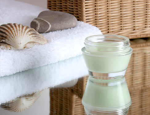 Cream in container next to shells on top of towel