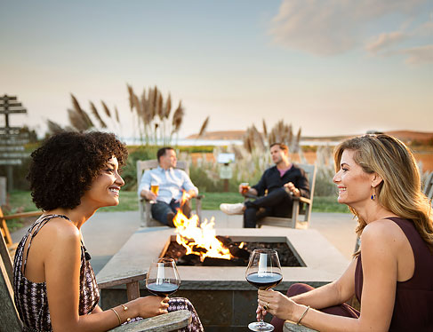 Two couples enjoying wine next to outdoor fire pit