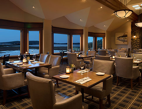 Drakes restaurant with tables set for meal next to large window panels with ocean view