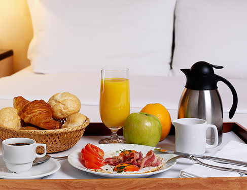 Eggs, bread basket, fruit, juice & coffee on table