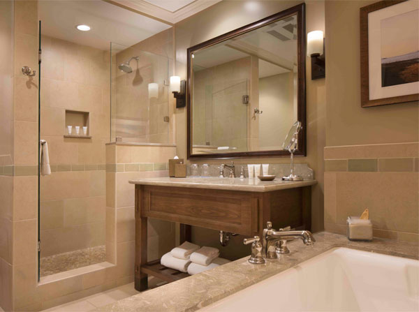 Full bathroom with tub, wooden built sink & glass shower