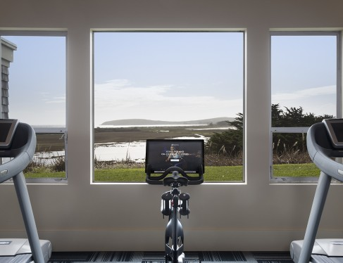 view of a stationary bike in front of three windows overlooking Doran beach