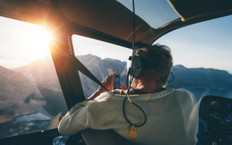 man in a helicopter taking a photo of the view