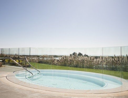 image of a hot tub in front of glass barriers