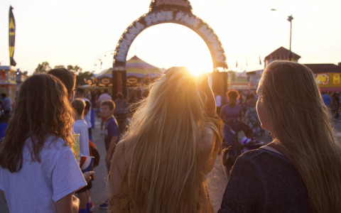 three women looking at the entrance of a fair at sunset