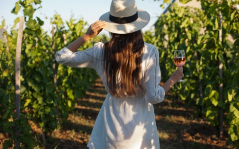 Woman walking through vineyards with glass of wine