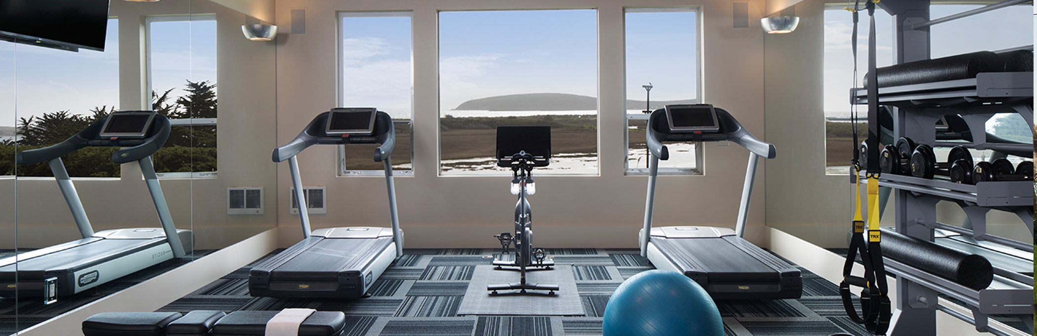 fitness center with two treadmills and a bike