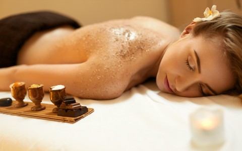 a woman enjoying a sugar scrub in the spa