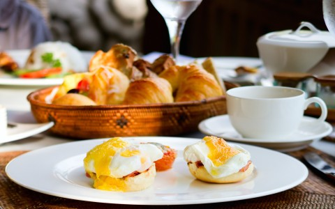 eggs benedict on a plate, croissants and coffee