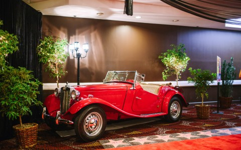 an antique red car on display in a room