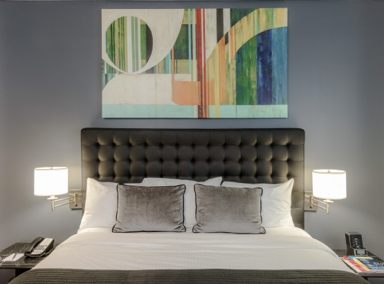 King-size bed, art above the bed, nightstands and lamps on each side, phone on the nightstand