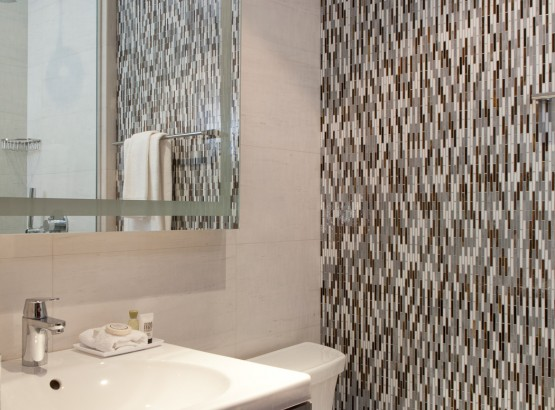 Bathroom with a glass door shower and tiled wall