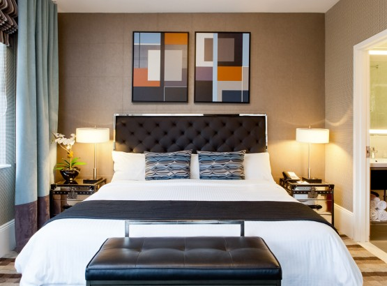King size bed with nightstands and lamps on each side, art above the bed, window to the left and bathroom on the right