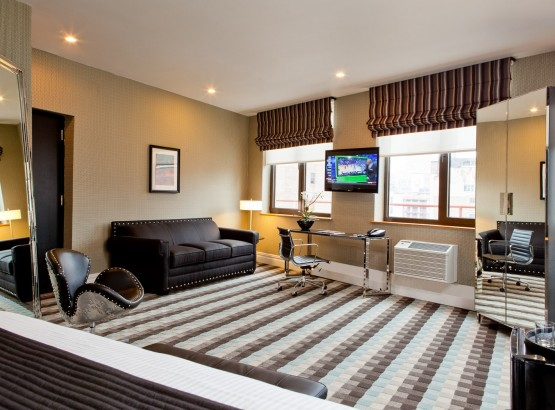 Suite with a black couch, silver studded chair, large floor length mirror, two windows, desk and chair, TV, wardrobe