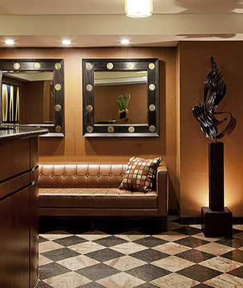Lobby with a brown leather couch, black and white checkered floor, two mirrors above the couch, statue on the right