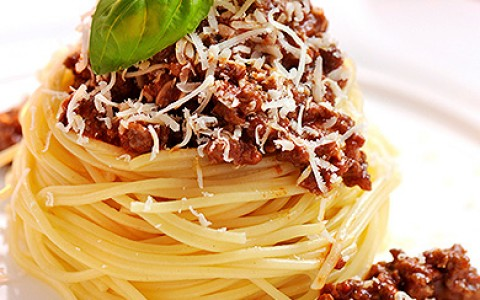 Spaghetti Bolognese garnished with fresh basil