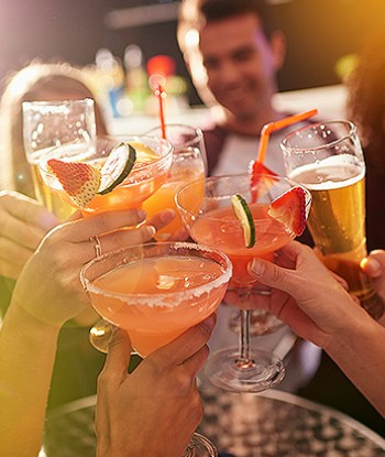 Group of people toasting with fruit cocktails and beer