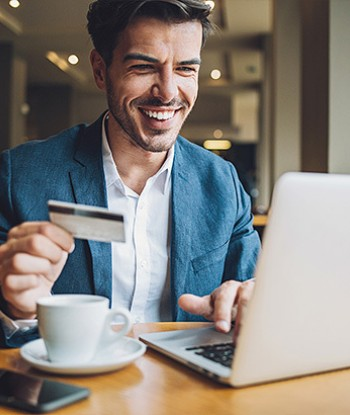 Man sitting in front of his labtop with a cup of coffee and credit card in hand