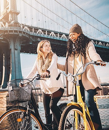Two women riding bikes near bridge