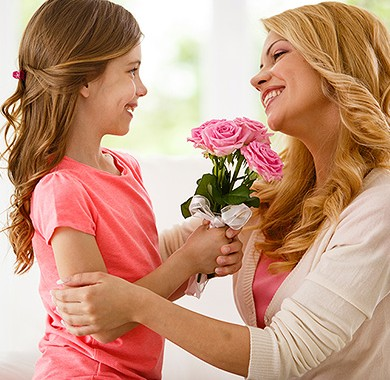 Daughter giving her mother pink roses as mother embraces daughter