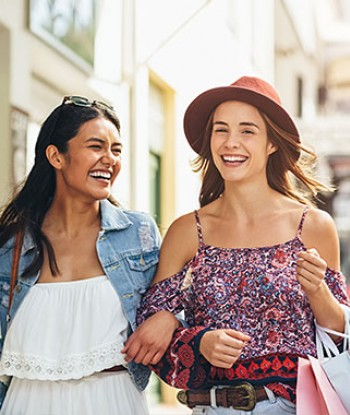 Two young women shopping and laughing