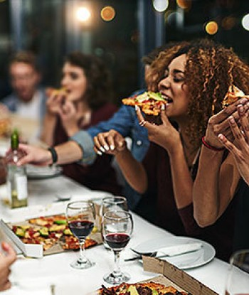 photo focused on two women biting into their pizza with glasses of wine on the table, people eating and drinking in the background