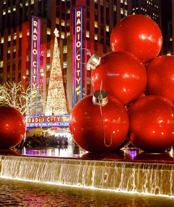 Radio City Music Hall at night time with large red ornaments in a water fountain surrounded by tree lights