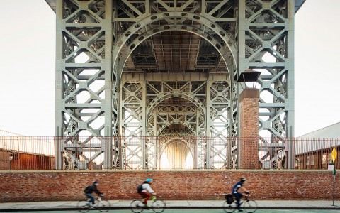 Three people riding their bikes under a bridge