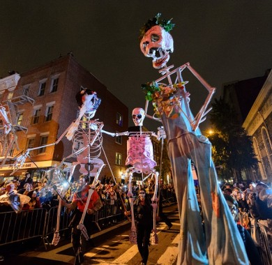 Large skeleton dolls being carried down the street during the Halloween Parade