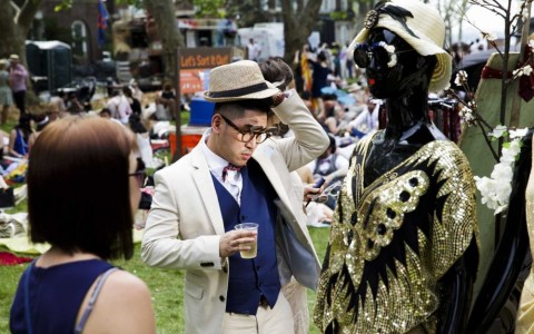 Man tries on hat at outdoor Jazz Age party