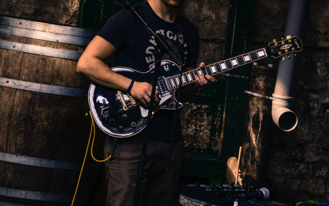Man playing a guitar in navy tshirt next to a barrel and a pipe