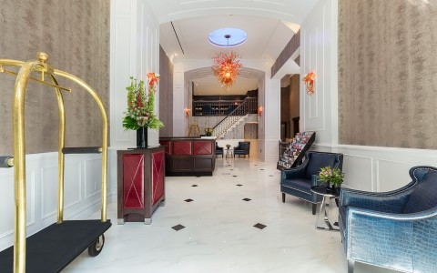 hotel lobby with a luggage cart and blue leather seats