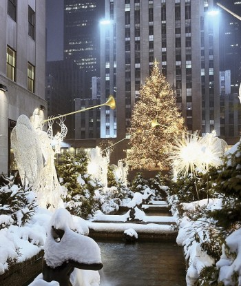 Rockefeller tree lit up at night time with angel statues and snow on the ground