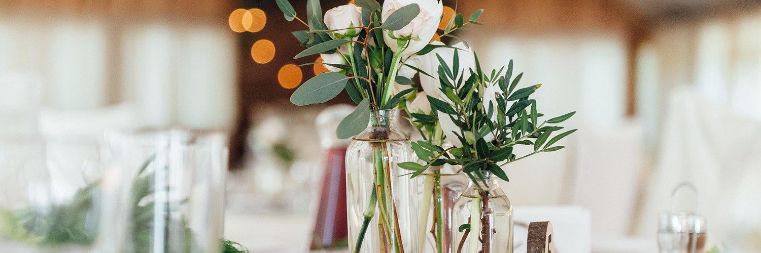Glass bottles with white roses on table