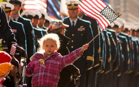 Child Waves American Flag at Veterans Day Parade