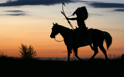 Silhouette of Native American on horseback shooting bow and arrow at sunset
