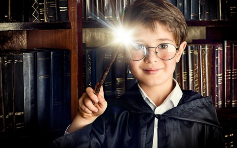 a boy stands with magic wand in the library by the bookshelves