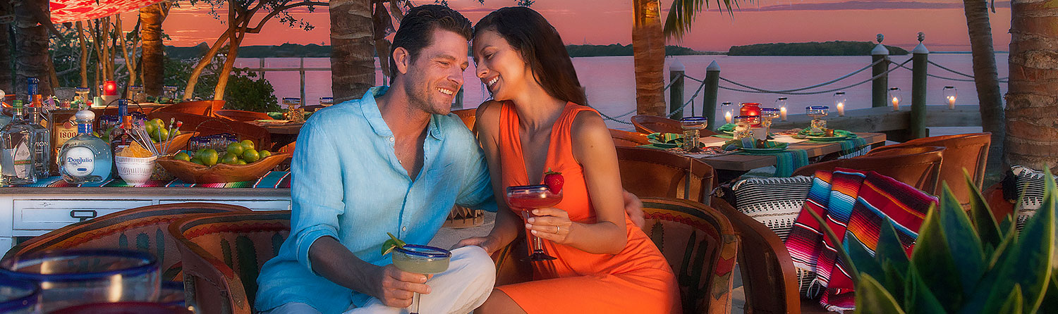Couple drinking cocktails in colorful outside seating area as the sun sets