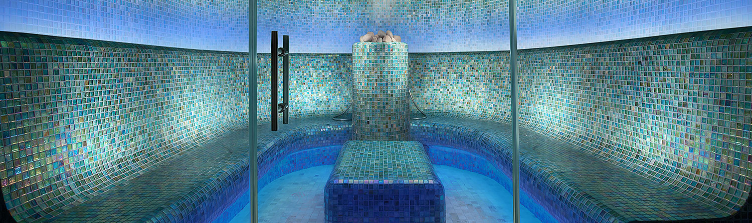 Indoor pool in spa with small aqua tones tiles on walls