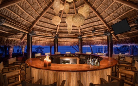 Large round tiki bar with seating around it by the water