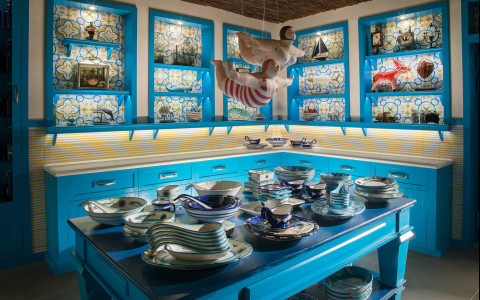 Open kitchen shelves with art decor and a blue island with blue plates and bowls