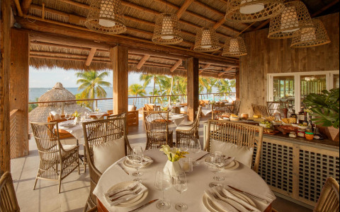 Round dining tables and chairs set up in a open restaurant with an ocean view