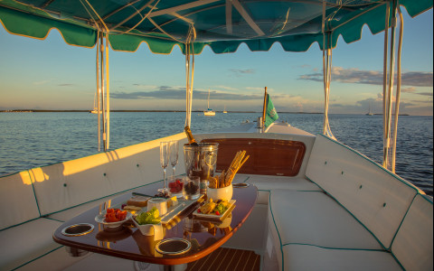 Boat on the water with a romantic spread of champagne, fruit and cheese