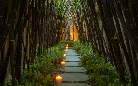Black bamboo walkway lit by candles with a buddha statue at the end