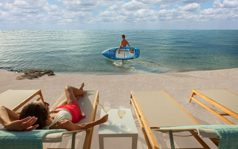 Woman laying on lounger on sand while man heads into the water with kayak boat
