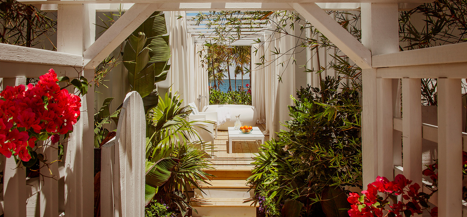Outdoor back porch with opened white wooden fence with fuchsia flowers leading to hot tub