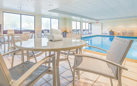 Table with towels & chairs next to indoor swimming pool