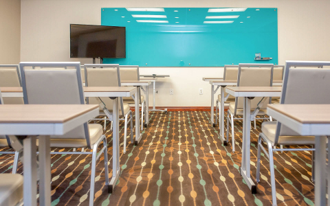 Meeting room with rectangular tables, blue dry erase board & TV